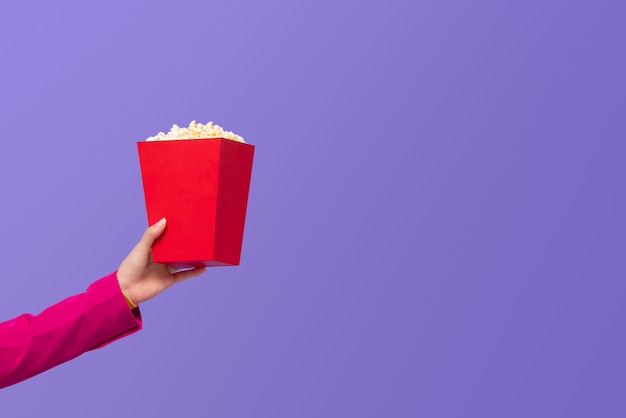 Woman hand giving popcorn in red box
