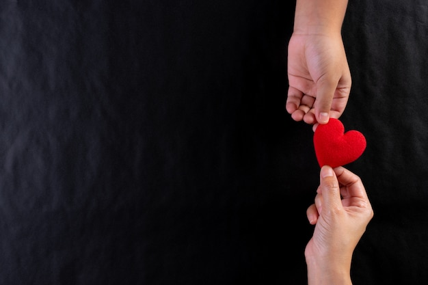 Woman hand giving red heart to child. international day of charity concept. copy space.