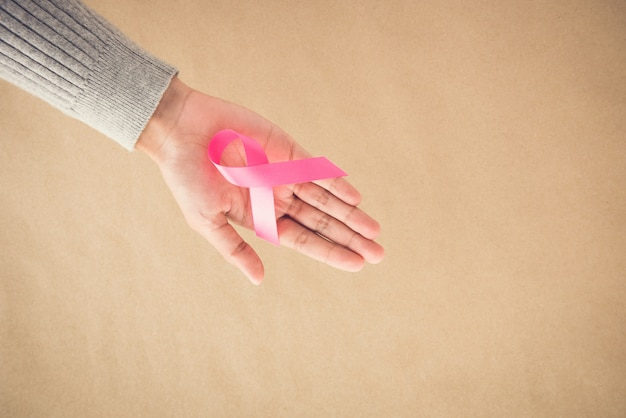 Woman hand giving satin pink ribbon, supporting symbol of breast cancer awareness campaign in october,