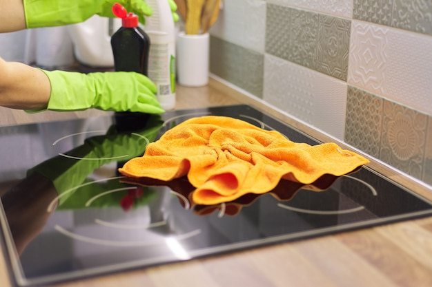 Woman hand in gloves cleaning kitchen electric ceramic hob, polishing glass with microfiber cloth
