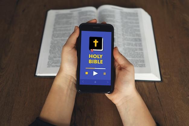 Женщина держит руку и сенсорный экран смартфон в церкви