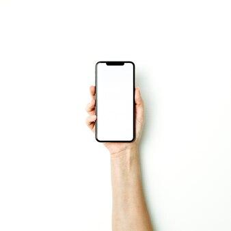 女性の手は空白のスマートフォンの画面を保持します。上面図