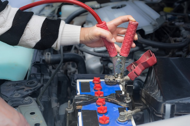 Woman hand hold jumper cables to car battery