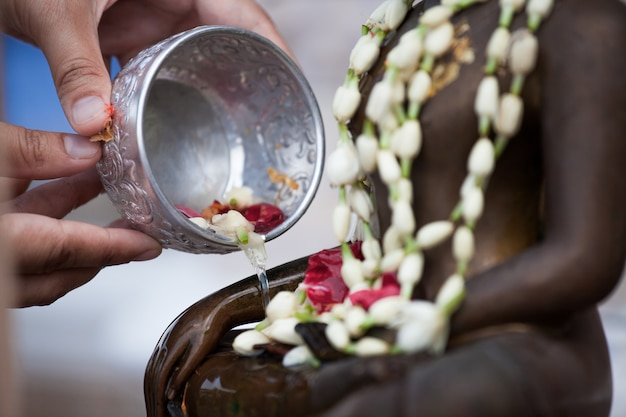 Woman hand hold little bowl to bath buddha statue for blessing ceremony celebrate songkran