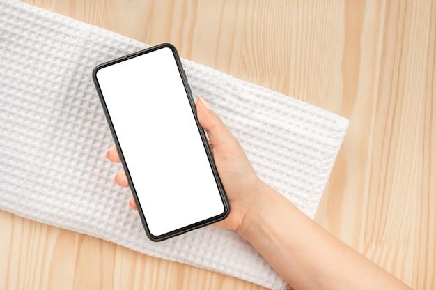 女性の手は、天然木のテーブルとスパトリートメント用の白いワッフルタオルに空白の画面でモックアップ携帯電話を保持します。スパと自然化粧品の広告の空白の白い画面
