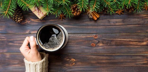 Женщина рука держать кружку кофе на черном деревянном рождестве