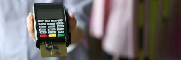 Женская рука держит pos termimal с золотой пластиковой дебетовой картой