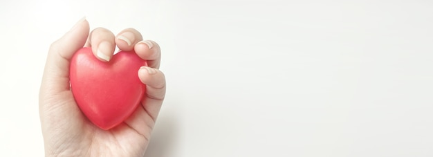 Woman hand hold red heart on the white background. health insurance, donation, saving life concept