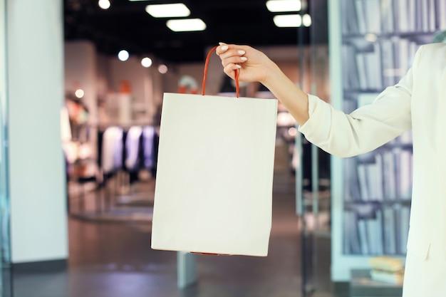 여자 손은 옷가게에서 쇼핑백을 들고 있습니다.