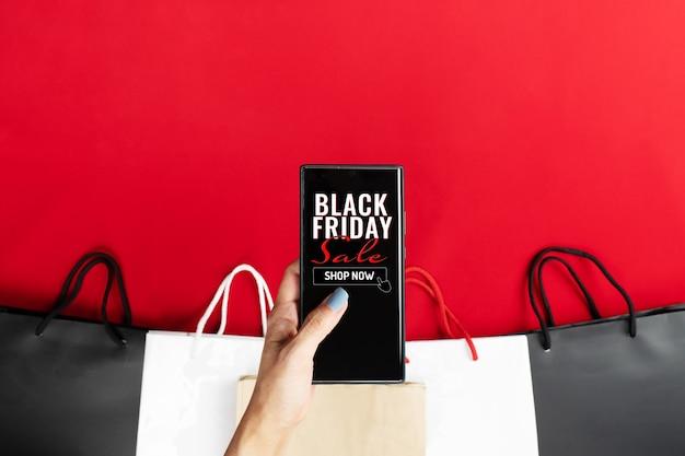 ブラックフライデーのオンラインショッピングのための女性の手持ちのスマートフォン