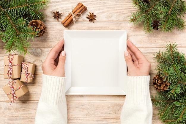 여자 손 잡고 상위 뷰입니다. 크리스마스 장식 나무 테이블에 흰색 사각형 접시. 새해 개념