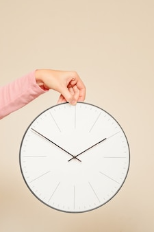 Woman hand hold wall clock on a white background