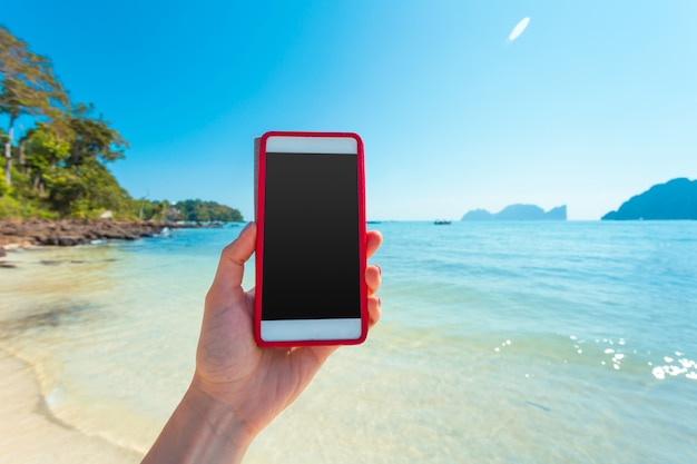 Woman hand hold white mobile phone with beautiful fresh sea and blue sky