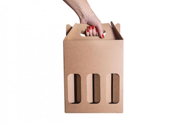 Woman hand holdind beer or vine cardboard box