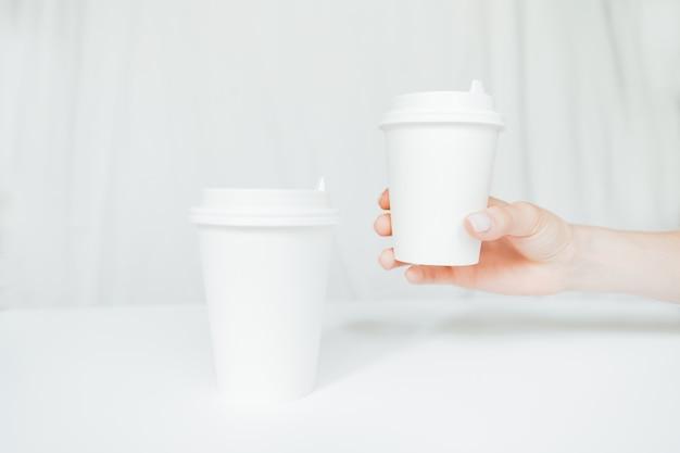 白い背景で隔離のコーヒー紙コップを持っている女性の手。