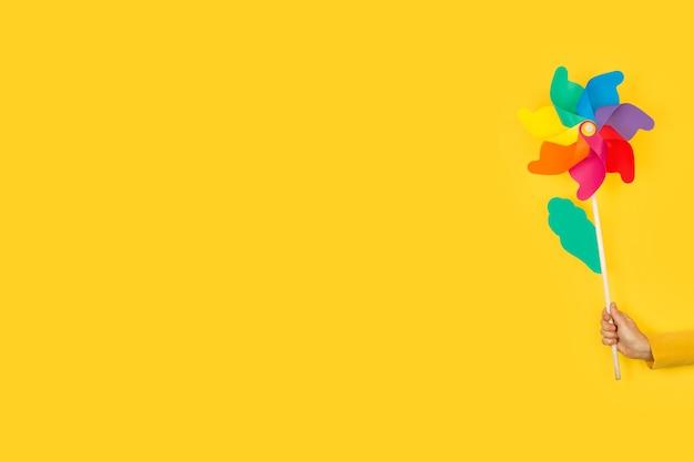 Женская рука держит цветную большую вертушку на желтом фоне