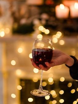 グラスワインを持っている女性の手。