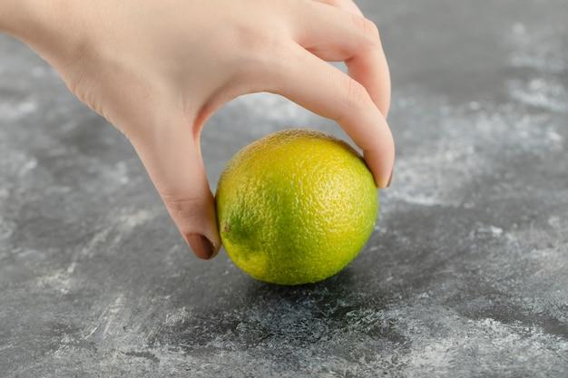 緑の新鮮なレモンを持っている女性の手。
