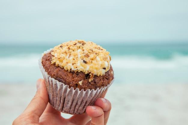 디저트와 스낵의 자연 개념을 배경으로 크림과 견과류를 넣은 머핀 컵케이크를 들고 있는 여성