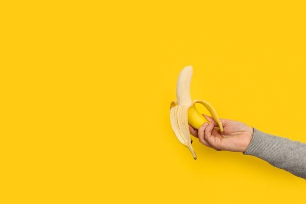 Женская рука держит очищенный банан на желтом фоне