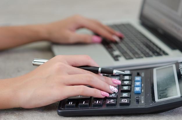 Рука женщины, держащая ручку и калькулятор. финансы, налоги и инвестиционный бизнес.