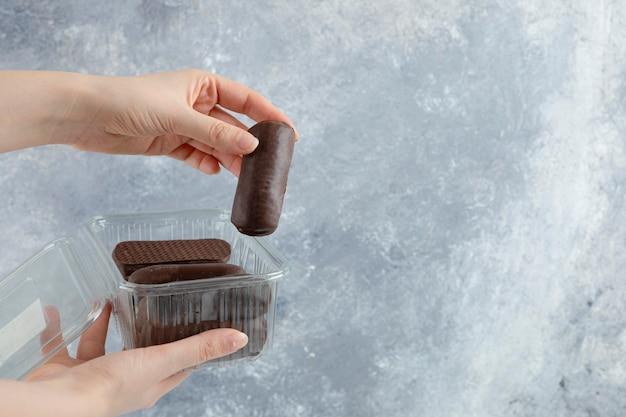 여자 손을 대리석 배경에 고립 된 초콜릿 크림 롤 플라스틱 상자를 들고.