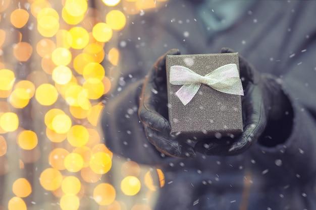 降雪時にクリスマスのぼやけた光の背景に弓で小さなギフトボックスを持っている女性の手。空きスペース