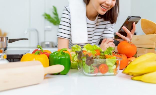 スマートフォンとトマトと自宅のテーブルで様々な緑の葉野菜のサラダボウルを持つ女性の手