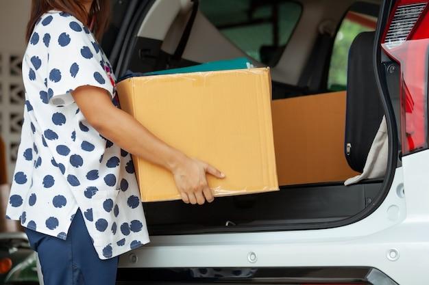 移動日に移動するために車に移動するものと一緒に段ボール箱を持って運ぶ女性の手