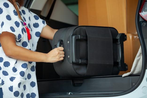 引っ越しの日に引っ越しのために車に移動するスーツケースを持って運ぶ女性の手