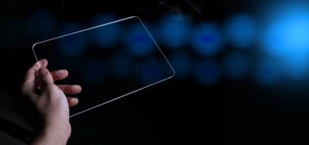 여자 손 잡고 추상 흐리게 bokeh 어두운 파란색 배경에 터치 스크린 스마트 폰, 태블릿 또는 핸드폰.