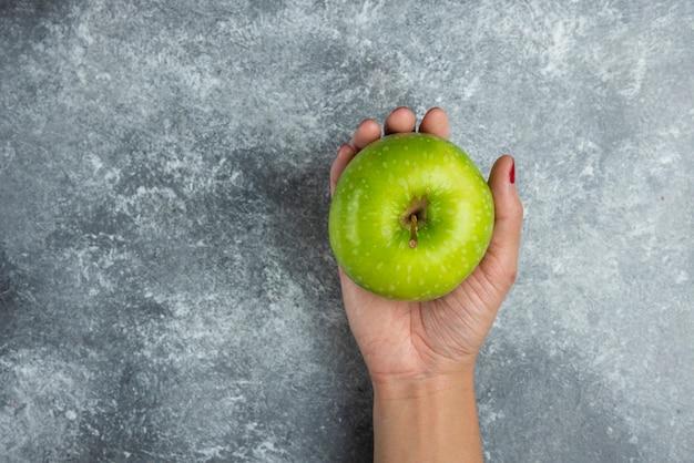Mano della donna che tiene mela su marmo.