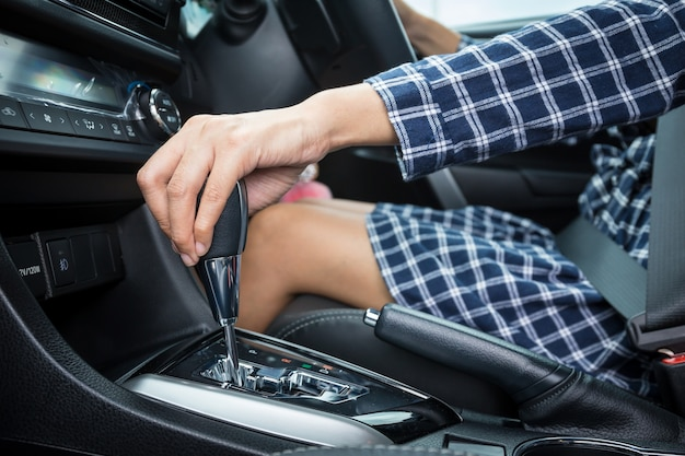Woman hand holding automatic gear shift in a car and wearing dress.