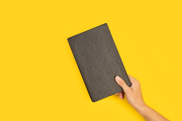 Woman hand holding a black book on a yellow background