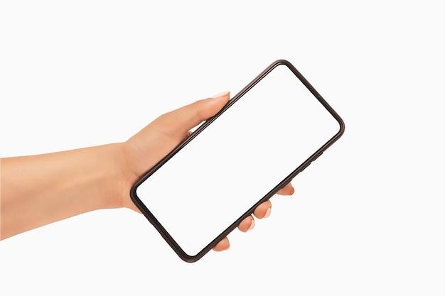 空白の白い画面とモダンなフレームレスデザイン-白い背景で隔離の黒い携帯電話のスマートフォンを持っている女性の手。モックアップ電話。携帯電話を持っている手