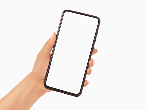 空白の白い画面とモダンなフレームレスデザイン-白い背景で隔離の黒い携帯電話のスマートフォンを持っている女性の手。モックアップ電話。黒のスマートフォンを持っている女性の手