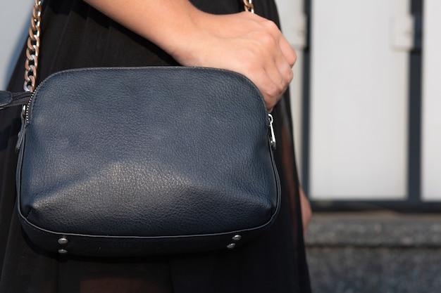黒革のハンドバッグを持っている女性の手