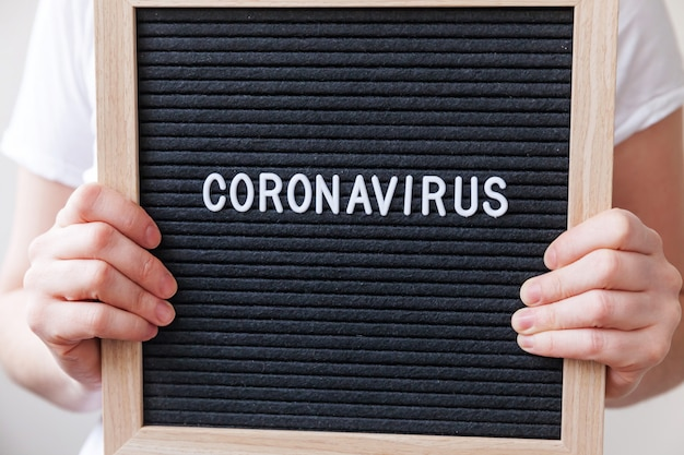 Woman hand holding black letter board with text phrase coronavirus.