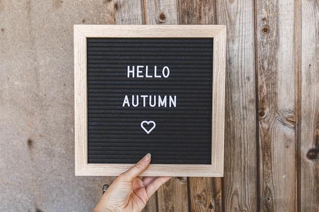 木製の手のひらにテキストフレーズこんにちは秋と黒い文字板を持っている女性の手