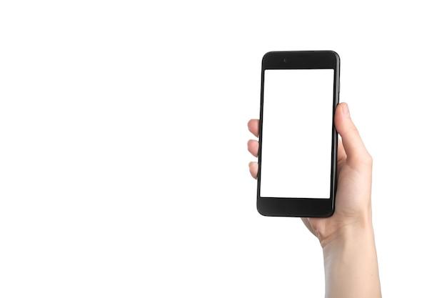 空白の白い画面と白い背景で隔離のモダンなフレームと黒いスマートフォンを持っている女性の手。