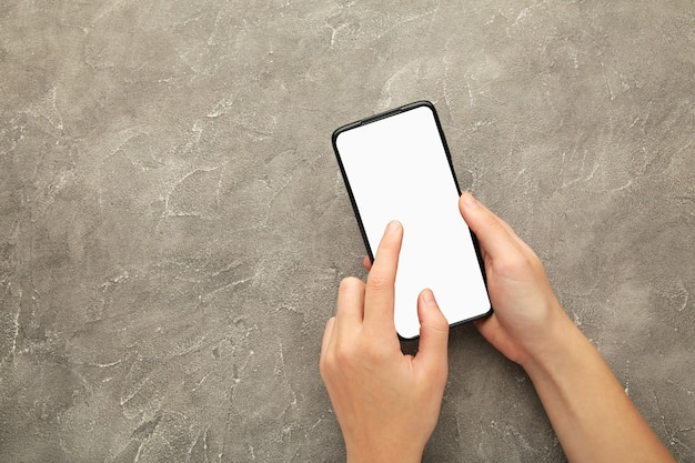 Woman hand holding the black smartphone with white screen