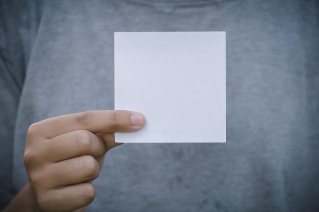 自然の背景に白紙を持っている女性の手。