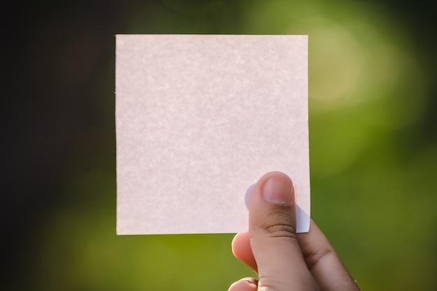 Рука женщины держа чистый лист бумаги на космосе природы.