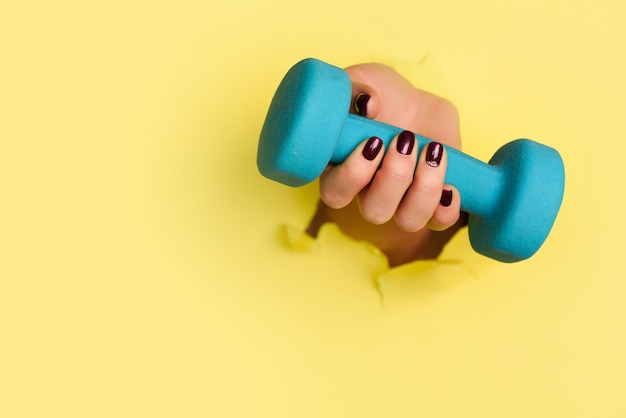 Woman hand holding blue dumbbell on yellow background.