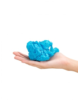 Woman hand holding blue plastic bag in ball composition isolated on white background.