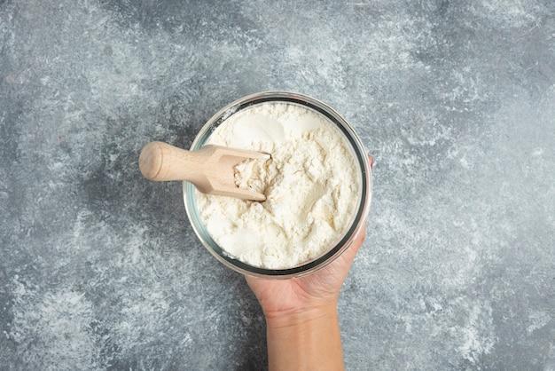 大理石に小麦粉のボウルを持っている女性の手。
