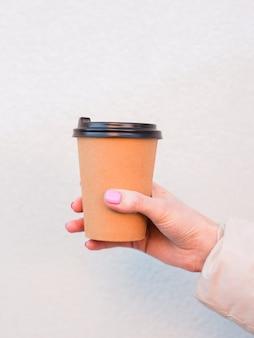 Рука женщины держа кофейную чашку коричневой бумаги напольную.