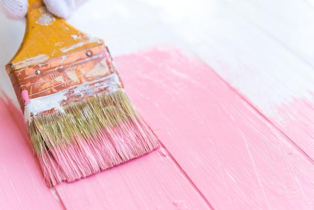 여자가 손을 잡고 흰색 나무 테이블에 브러쉬 페인팅 핑크 색상