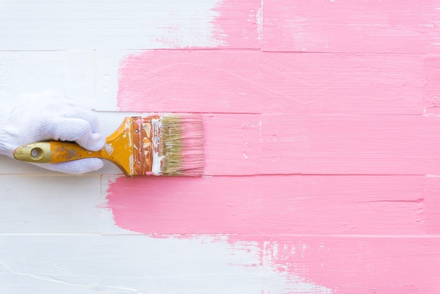 Woman hand holding brush painting pink color on a white wooden table