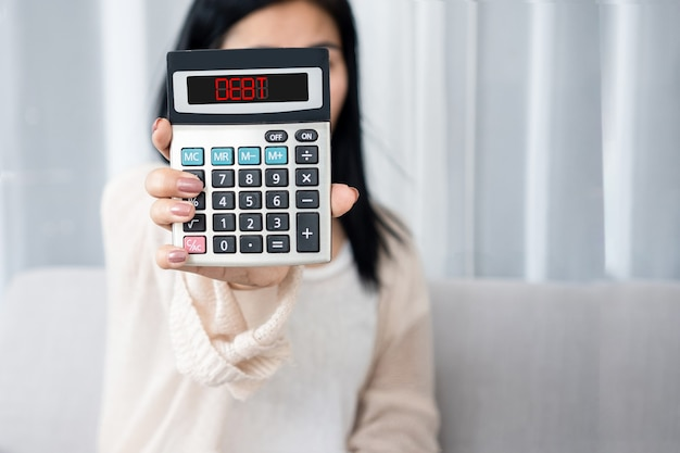 Woman hand holding calculator showing word debt   financial problem concept